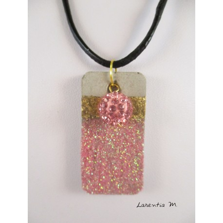 Shamballa bead necklace pendant pink on concrete pedestal decorated rectangle glittery pink and gold metal sheet