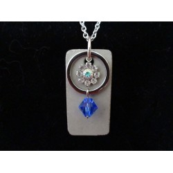 Necklace with Swarovski crystal ring and blue beads on concrete pad