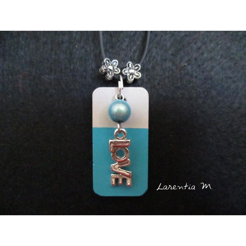 """Collier pendentif """"Love"""" avec perle bleue sur socle de béton rectangle peint turquoise"""