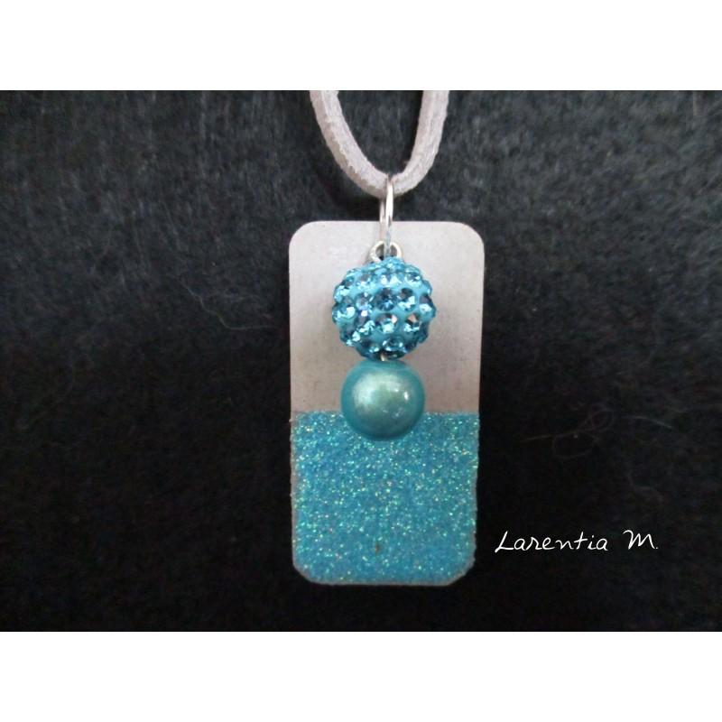 Collier pendentif perle Shamballa bleue et perle magique bleue sur socle de béton rectangle peint bleu avec paillettes