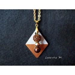 Collier pendentif perles shamballa marron, dorée et cirée marron sur socle de béton losange peint bronze