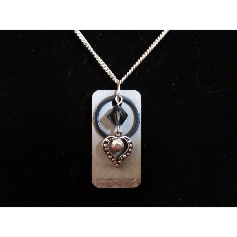 Collier pendentif avec perles cristal Swarosvki noire, anneau et coeur argent sur socle de béton