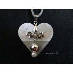 Collier pendentif avec perles cirées argent/blanche, suspendues à un noeud papillon, sur socle de béton coeur blanc pailleté