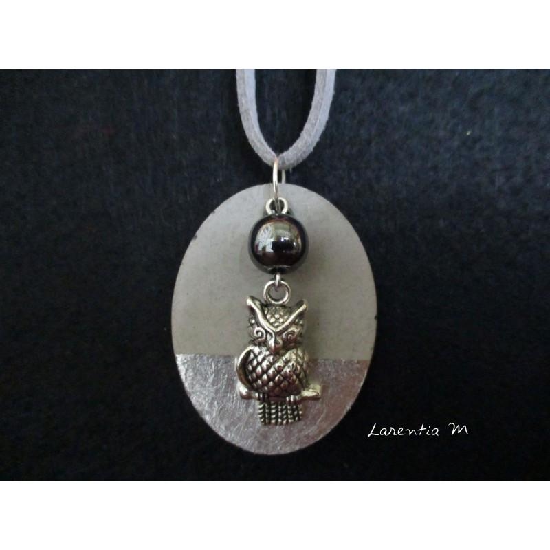 """Collier, pendentif """"Chouette""""avec perle hématite noire sur socle de béton avec bas argenté"""