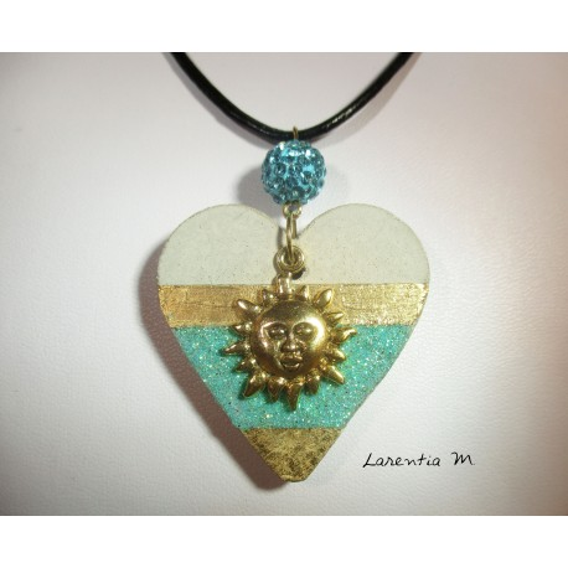 Collier pendentif avec soleil doré, suspendue à une perle shamballa bleue sur coeur béton pailleté et doré à la feuille métal